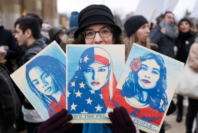 "International Women's Strike (Getty) TOPSHOT - An anti-Trump protester hold signs during a demonstration against Trump's policies in front of the Eiffel Tower in Paris, on February 4, 2017. US President Donald Trump lashed out on February 4, 2017 at a court ruling suspending his controversial ban on travelers from seven Muslim countries, dismissing it as ""ridiculous"" and vowing to get it overturned. The order blocking the ban, issued late on February 3, 2017 by Seattle US District Judge James Robart, is valid across the United States, pending a full review of a complaint filed by Washington state's attorney general. / AFP / THOMAS SAMSON (Photo credit should read THOMAS SAMSON/AFP/Getty Images)"
