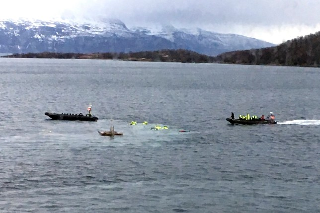 A boat picks up tourists from the water after an accident in Harstad harbour in Northern Norway, Thursday Feb. 16, 2017. Nearly two dozen people, mostly British tourists have been injured after a boating accident in the Norwegian coastal town of Harstad, local media report. The accident is believed to have happened when one of two small speedboats hit a water fountain installation. The fountain _ which sends water 60 meters into the air _ was not functioning at the time of the accident, according the Norwegian Aftenposten news site. (Gunnar Berg /NTB scanpix via AP)
