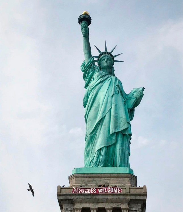 """In this photo provided by VitÛria Londero, a giant banner saying """"Refugees Welcome"""" hangs on the pedestal of the Statue of Liberty, Tuesday, Feb. 21, 2017, in New York. National Park Service spokesman Jerry Willis says the banner was hung from the public observation deck at the top of the statue's pedestal Tuesday afternoon. (VitÛria Londero via AP)"""