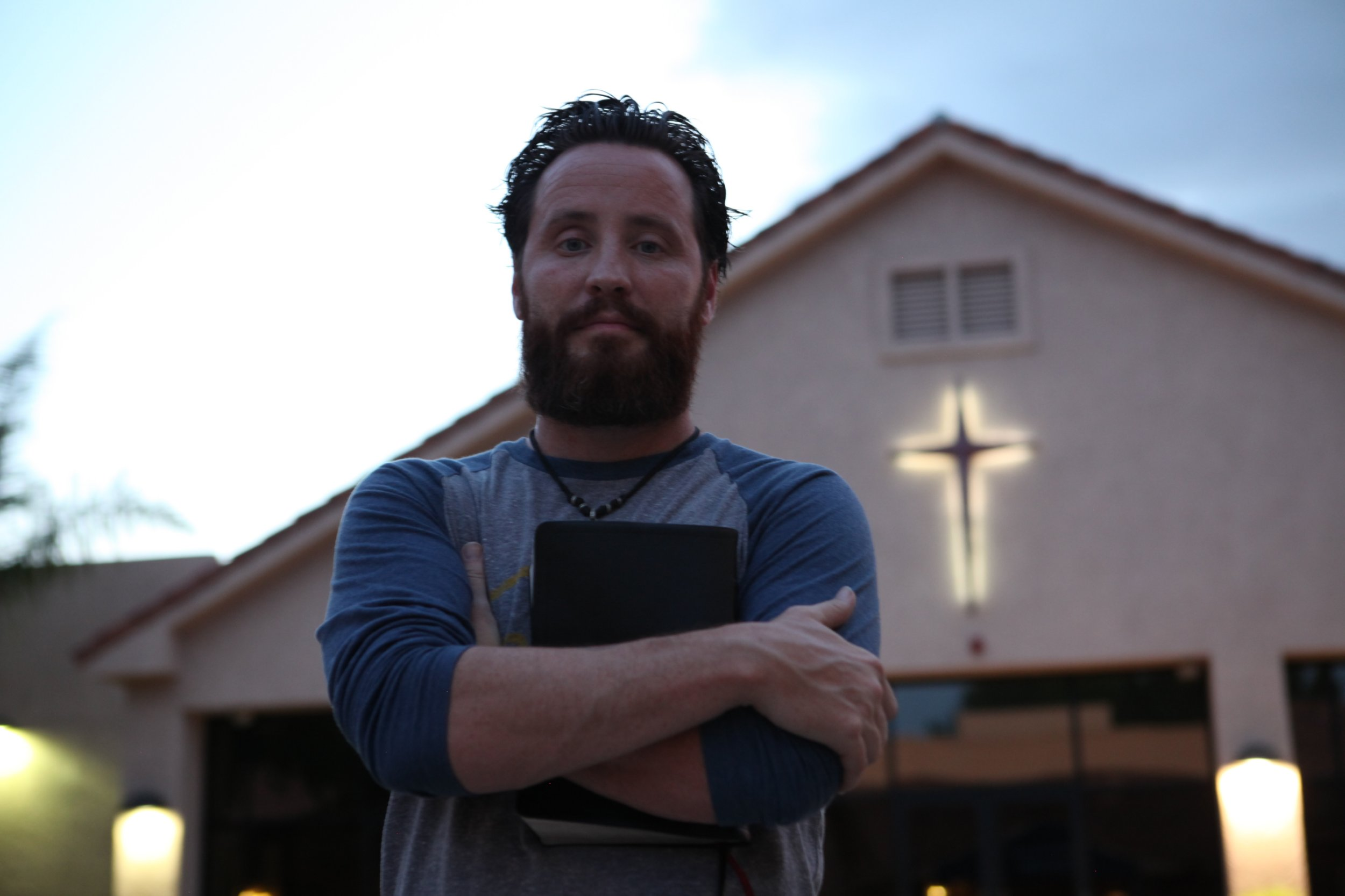 *** EXCLUSIVE - VIDEO AVAILABLE *** TEMPE, AZ - AUGUST 1: Jeff Durbin, pastor at Apologia Church, clutches a Bible to his chest in front of the church building, complete with glowing cross, on August 1, 2016, in Tempe, Arizona. A MODERN pro-life church who believe that women should get the death penalty for intentionally aborting their babies are looking to change the face of the anti-abortion movement in the US. With his immaculately groomed beard, tattoos and Aviator sunglasses, the Red Door Ministryís telegenic pastor, reformed drug addict Jeff Durbin, 38, looks every inch the young, modern-day American hipster. But the groupís views are resolutely old school - they say abortion is ëworse than the Holocaustí and regularly enlist children as young as two to picket Planned Parenthood clinics, armed with signs reading 'Babies are murdered hereí. Based in Tempe, Arizona, the ministry is run by the Apologia Church, a militantly pro-life group campaigning to overturn Roe v Wade, the landmark 1973 Supreme Court ruling that gave women a constitutional right to an abortion in the early stages of pregnancy. The churchís critics accuse it of intimidating women seeking an abortion, but with US president Donald Trump pursuing an aggressively pro-life agenda, pro-choice campaigners fear the right to a legal abortion in the US may be under threat. PHOTOGRAPH BY Ruaridh Connellan / Barcroft Images London-T:+44 207 033 1031 E:hello@barcroftmedia.com - New York-T:+1 212 796 2458 E:hello@barcroftusa.com - New Delhi-T:+91 11 4053 2429 E:hello@barcroftindia.com www.barcroftimages.com