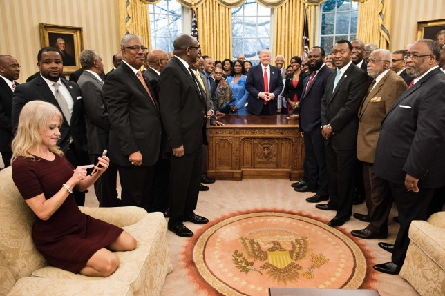 Counselor to the President Kellyanne Conway (L) checks her phone after taking a photo as US President Donald Trump and leaders of historically black universities and colleges pose for a group photo in the Oval Office of the White House before a meeting with US Vice President Mike Pence February 27, 2017 in Washington, DC. / AFP PHOTO / Brendan SmialowskiBRENDAN SMIALOWSKI/AFP/Getty Images