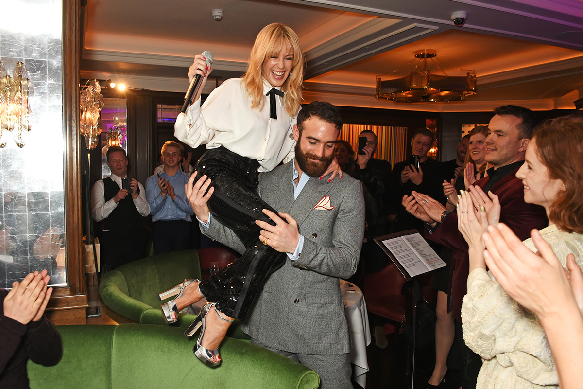 LONDON, ENGLAND - DECEMBER 07: Kylie Minogue (L) and Joshua Sasse attend an intimate performance with Kylie Minogue at The Ivy to kick off The Ivy 100 Centenary celebrations on December 7, 2016 in London, England. (Photo by David M. Benett/Dave Benett/Getty Images for The Ivy)