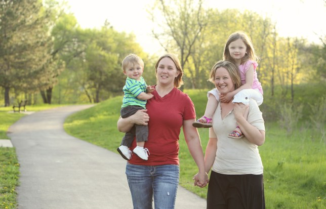 Two beautiful lesbian moms hold hands while taking their boy and girl children for a walk outdoors in the park on a sunny day. The family has light brown and blonde hair and the kids are adorable.