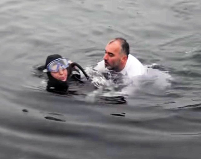 Pic shows: Ismail Yildirim the mayor is rescuing the diver.nnBy Mert SunnThis is the incredible moment a mayor interrupts a civic ceremony to dive off a pier and save a scuba diver who had fainted in the water.nnIsmail Yildirim, mayor of the town of Karamursel in north-western Turkey's Koceli Province, was attending a ceremony to mark the anniversary of a ferry disaster.nnTwo divers were in the sea to place a wreath on the water in tribute to the 272 people who lost their lives in the Uskudar Disaster of 1958.nnOnlookers could hardly believe their eyes when Mayor Yildirim suddenly pulled off his shoes, tie and jacket and jumped into the water with an enormous splash.nnHe had spotted that one of the scuba divers, a woman called Senay Ertorun, had fainted in the water and was in difficulties.nnThe mayor, who is himself a qualified diver, swam over to the woman and pulled her to the shore.nnOnlookers pulled her, and her rescuer, on to dry land before handing the mayor a blanket so that he did not get too cold.nnThe mayor's quick-thinking and selfless actions in jumping into the cold water earned him a round of applause from the watching crowd.nnMs Ertorun was treated at the scene and has made a good recovery.nnThe incident was captured on camera by eyewitnesses with smartphones and the footage is already proving popular on social media and video-sharing websites.nnThe Uskudar Disaster involved the sinking of a small passenger ferry, the German-built SS Uskudar, in the Gulf of Izmit in March 1958, with the loss of 272 lives.nnKaramürsel is historically known as the Town of The Wrestlers, and is also renowned for its fish restaurants and for its handmade silk carpets including the famous Hereke rugs.nn(ends)