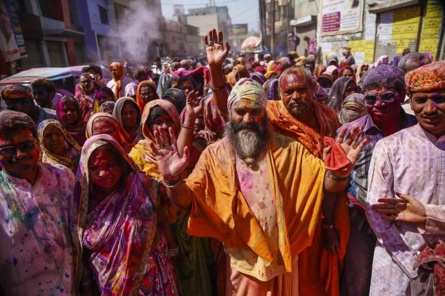 VRINDIVAN, INDIA - MARCH 24: Indians take part in the Holi Festival celebrations in Vrindivan, 120 km far from New Delhi, India on March 24, 2016. Holi, the festival of colors, is a riotous celebration of the coming of spring and falls on the day after full moon annually in March. Revelers spray colored powder and water on each other with great gusto, whilst adults extend the hand of peace. (Photo by Fatih Aktas/Anadolu Agency/Getty Images)