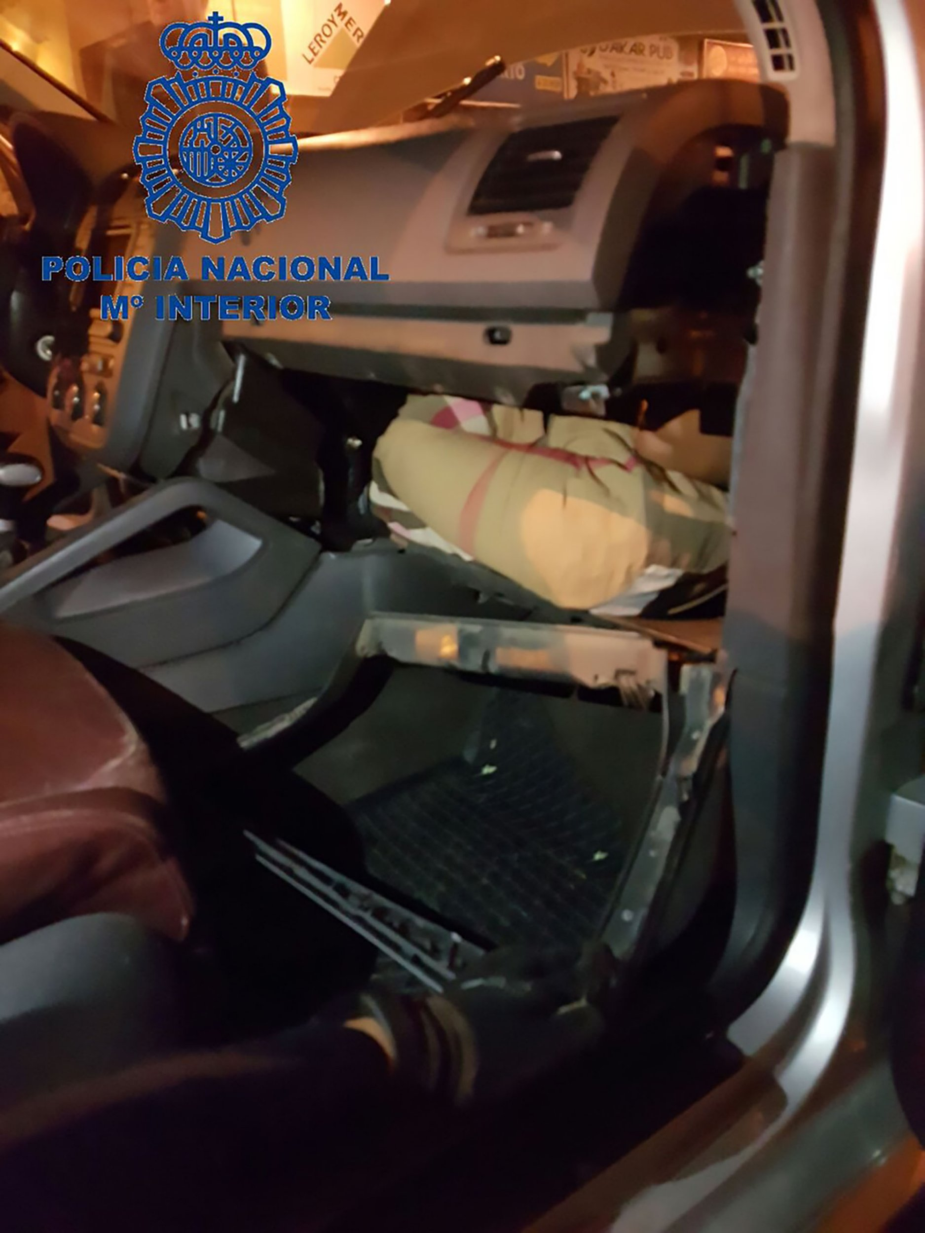 """Pics shows: Two men attempted to cross the border into the Spain's north African enclave of Ceuta on Friday night;nnBorder police were surprised to find a hidden migrant crammed inside a car¿s dashboard.nnThe driver, identified only as a 36-year-old named R.M.S, has been arrested after the bizarre find by Spanish officers which happened on the border joining Spain with north Africa in the city of Ceuta.nnTwo migrants were found inside the vehicle - a man was hiding under the seat and a woman was curled up inside the dashboard.nnThe driver is alleged to have been a Spanish national who had offered to help the desperate asylum seekers for money.nnHis vehicle was searched after officers said he was behaving """"nervously"""".nnBecause of his weird behaviour, officers decided to check the entire vehicle carefully and found some evidence that the seat and the front part of the vehicle had been """"manipulated"""".nnThey searched the glove box of the vehicle and found the woman who they say had clear symptoms of suffocation and had fainted.nnA man was also hidden under the back seat of the car.nnOfficers say the unnamed migrants are both of Guinean origin and are between 18 and 20 years old.nnThe driver has been arrested and charged.nnThe case continues."""