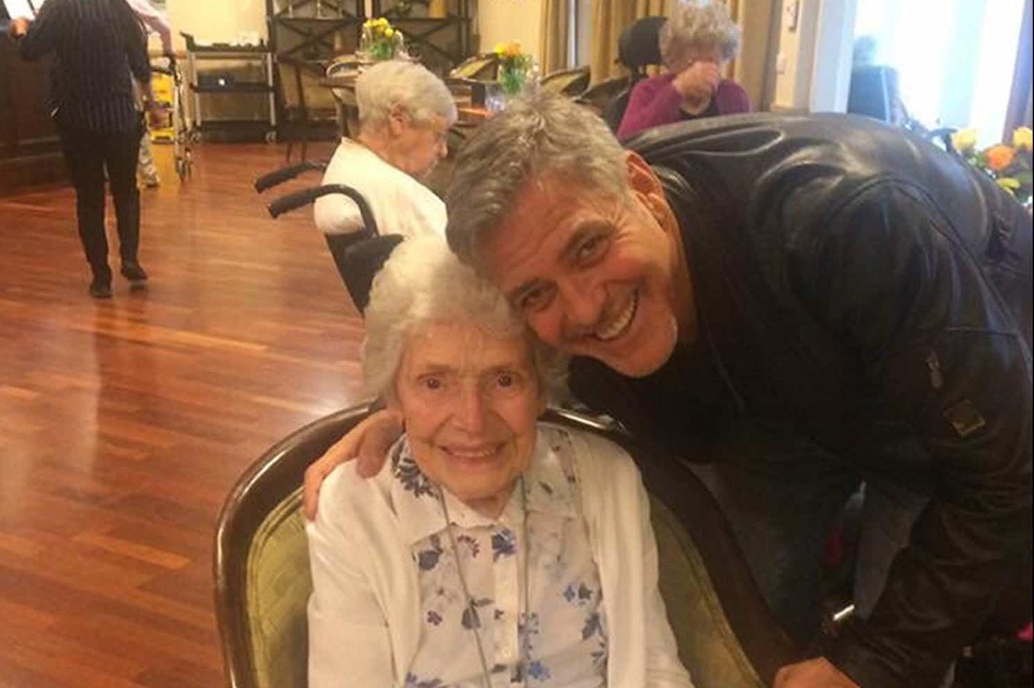 Undated Sunrise UK handout photo of George Clooney with Pat Adams. PRESS ASSOCIATION Photo. Issue date: Monday March 20, 2017. Actor George Clooney surprised a fan by visiting her in her assisted living home to wish her a happy 87th birthday. He brought with him a card and a bunch of flowers as he popped in for a chat and a picture with his long-time admirer Pat Adams on Monday. Linda Jones, a worker at the Sunrise Sonning Retirement and Assisted Living Facility, posted a picture of the beaming pair on Facebook. See PA story SHOWBIZ Clooney. Photo credit should read: Sunrise UK/PA Wire NOTE TO EDITORS: This handout photo may only be used in for editorial reporting purposes for the contemporaneous illustration of events, things or the people in the image or facts mentioned in the caption. Reuse of the picture may require further permission from the copyright holder.