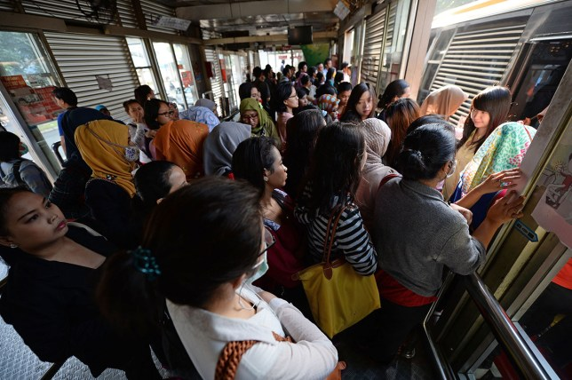 Morning commuters wait to board a TransJakarta bus in 2014(Picture: Dimas Ardian/Bloomberg via Getty Images)