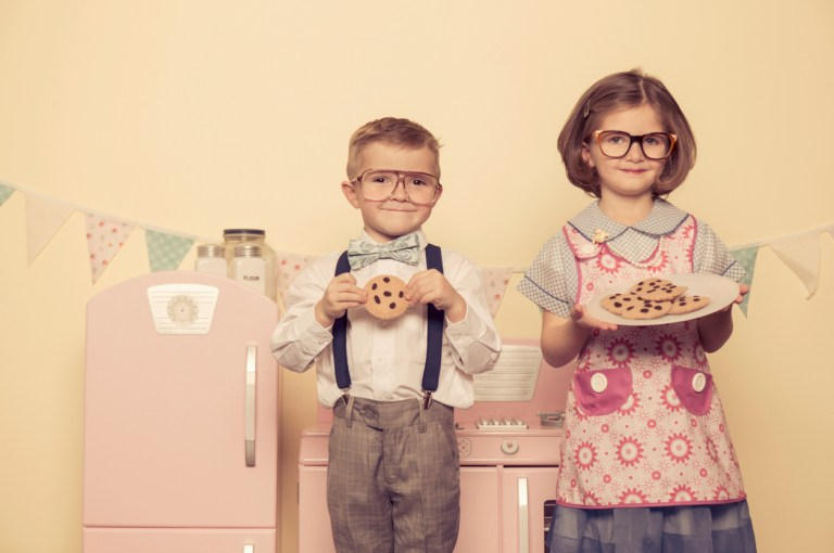 Two children dressed as a married couple love cookies.