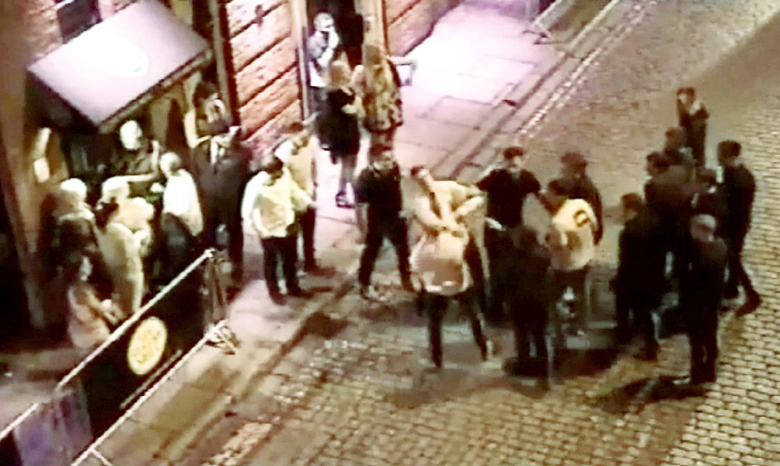 Football fans clash in shocking CCTV footage filmed outside nightclub