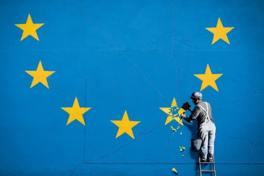 A blue and yellow Banksy mural depicting Brexit. The yellow stars of the EU flag are being chipped away by a painter