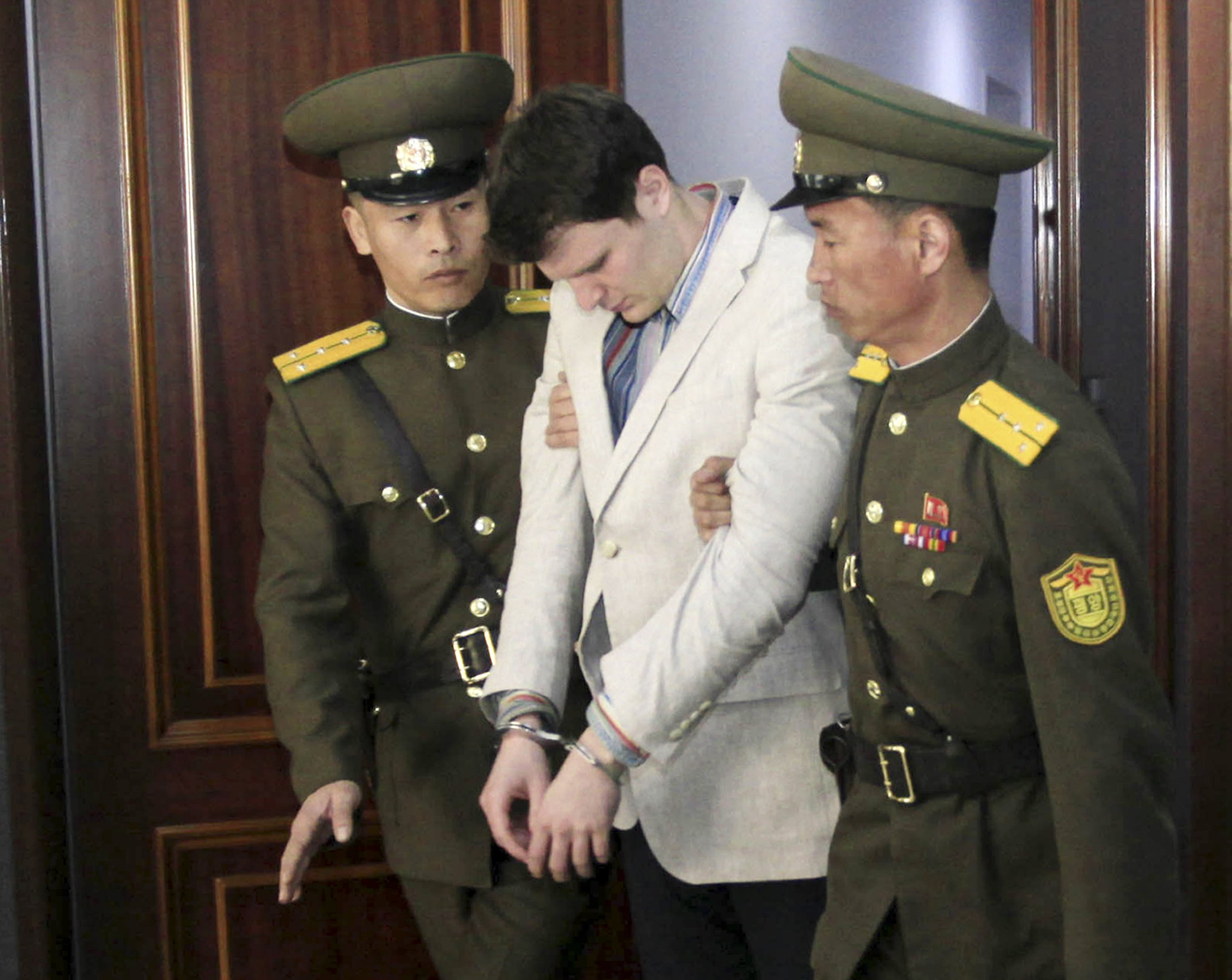 Otto Warmbier in handcuffs next to two North Korean officials