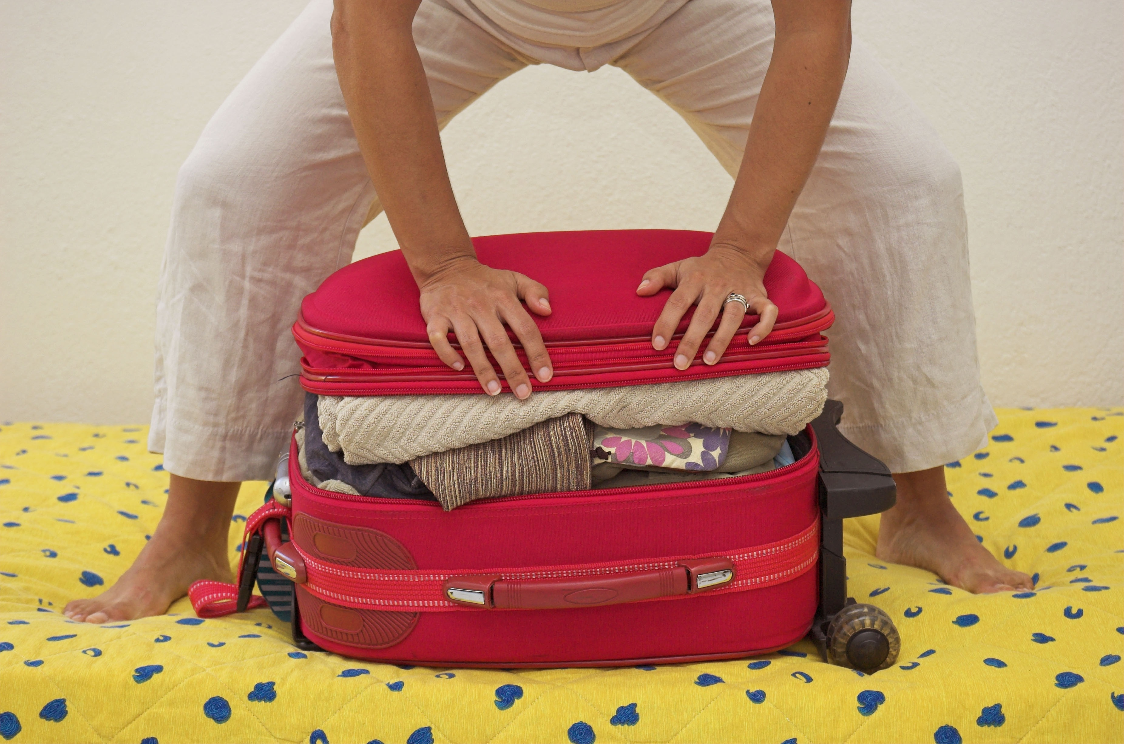 Woman trying to squeeze her packed travel case shut.