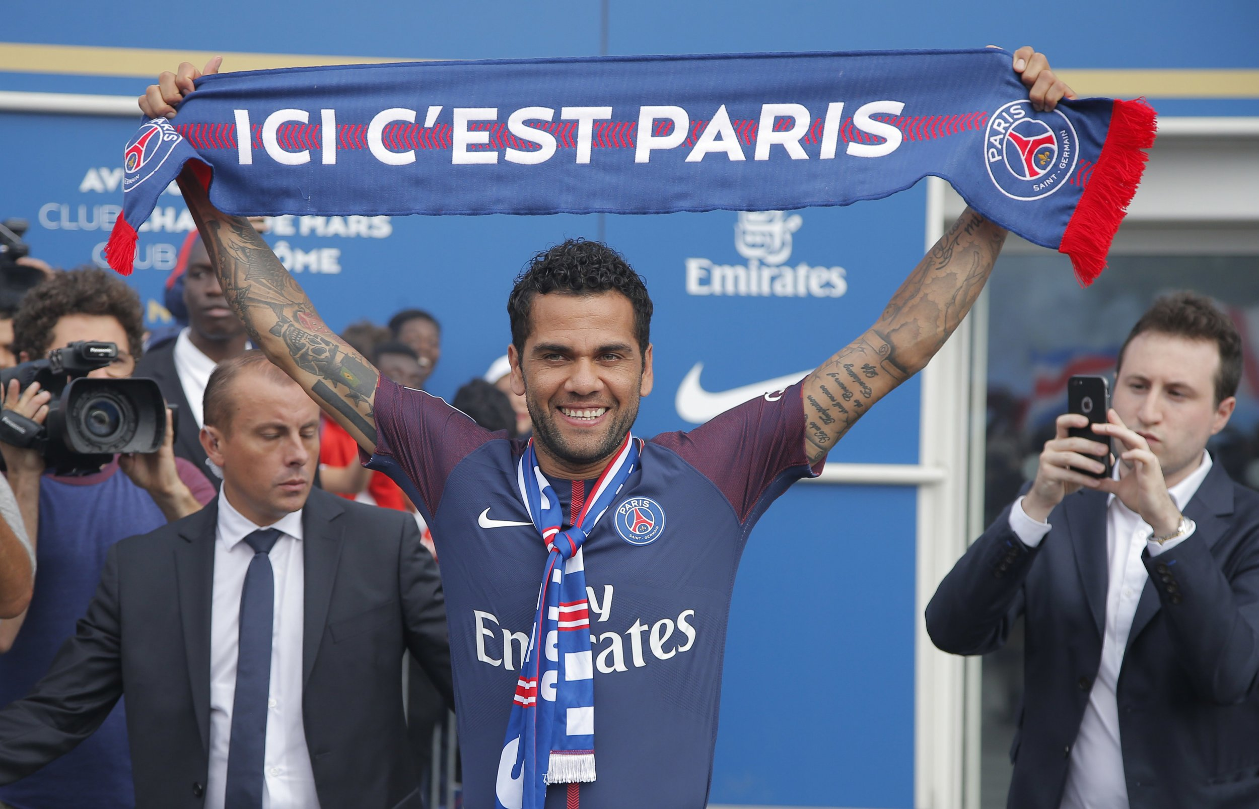 "Brazilian soccer player Dani Alves holds a scarf which reads ""this is Paris"" as he acknowledges applauded of supporters after a media conference at Parc des Princes stadium in Paris, France, Wednesday, July 12, 2017. Dani Alves has agreed to join Paris Saint-Germain from Juventus on a two-year deal. (AP Photo/Michel Euler)"