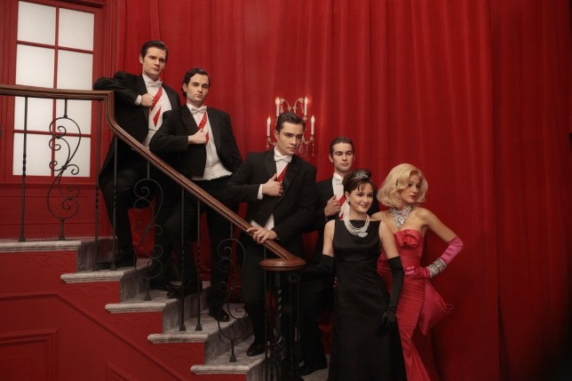 Six of The Gossip Girl cast posing together in tuxedos and smart ball gowns in front of a red curtain