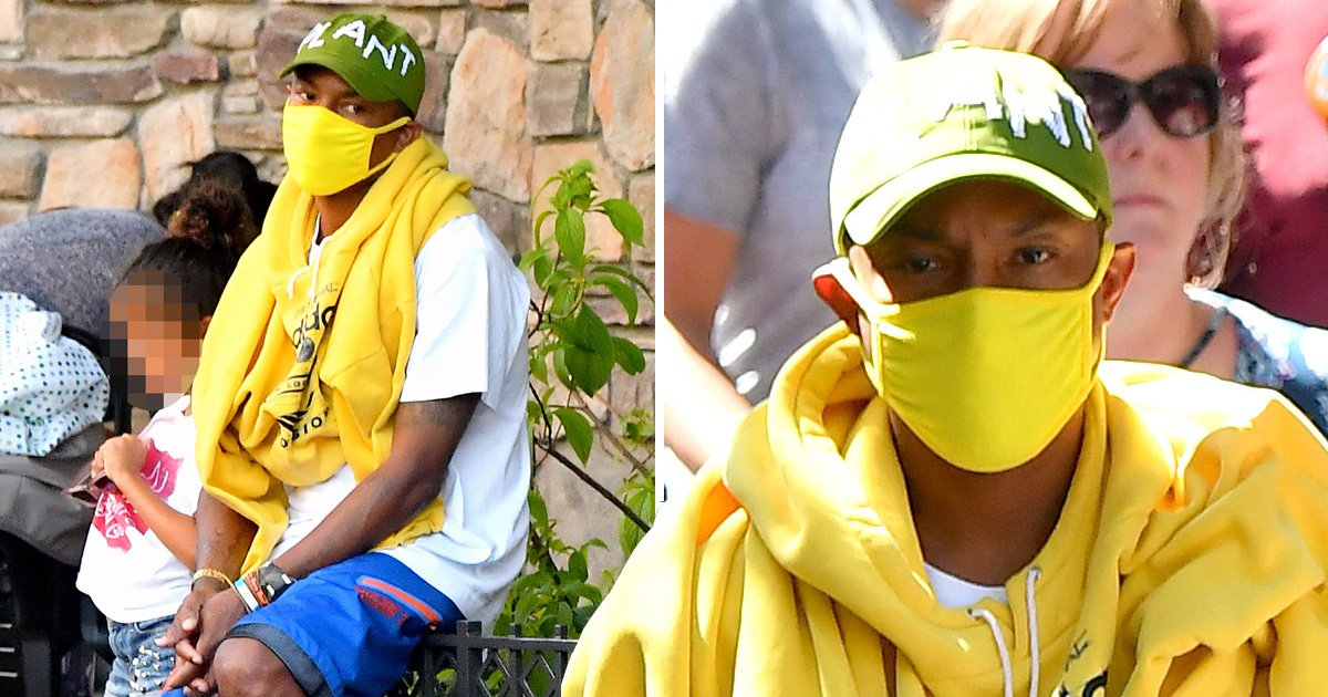 Pharrell Williams co-ordinates his surgical mask to his hoodie and trainers at Disneyland