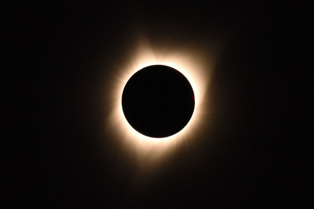 The sun's corona is visible as the moon passes in front of the sun during a total solar eclipse (Getty)