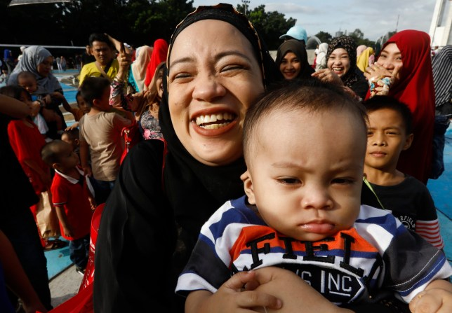A Muslim woman smiles while holding a baby