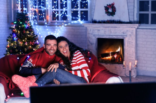 Young couple on the sofa watching TV by a fireplace with a christmas tree