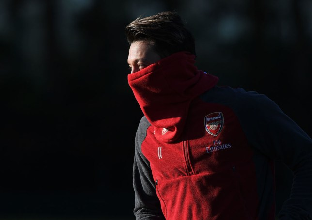 Mesut Ozil trains with his neck warmer wrapped up around his nose