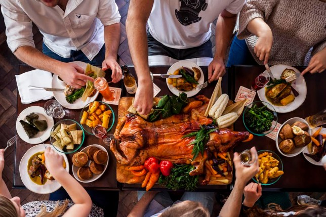 Friends sharing a meal with a centrepiece of a roast sucking pig and an assortment of sides