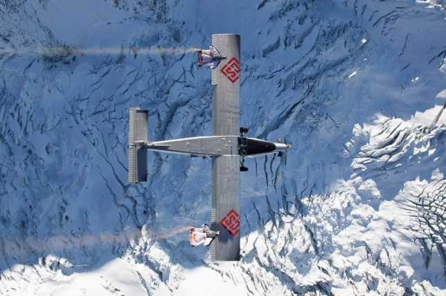 Two wingsuit flyers base jump into a plane in mid-air