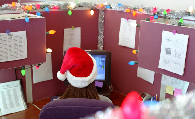 Woman in office cubicle alone wearing a Santa hat