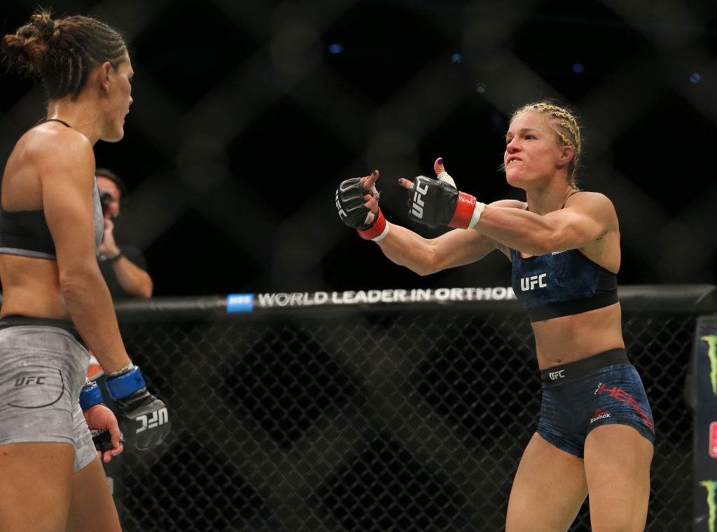 Cortney Casey and Felice Herrig give each other the middle finger in the middle of their UFC 218 fight