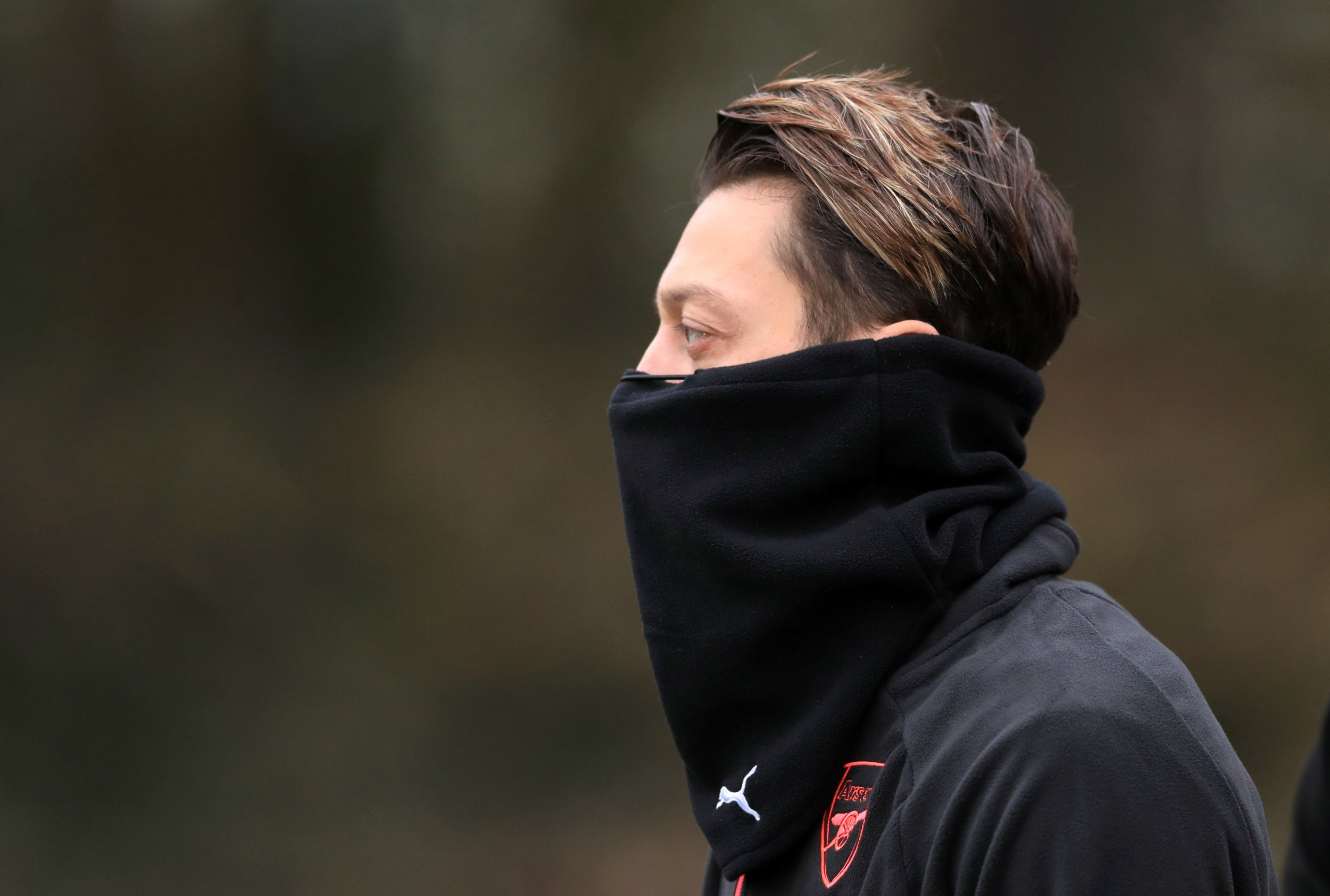 Mesut Ozil pictured from the side with his hood over his mouth