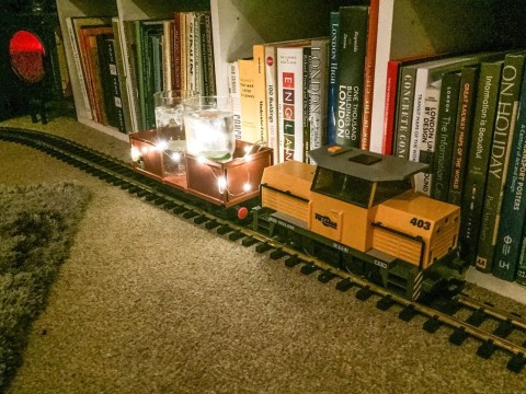 Genius man uses toy train to transport drinks around his Christmas party