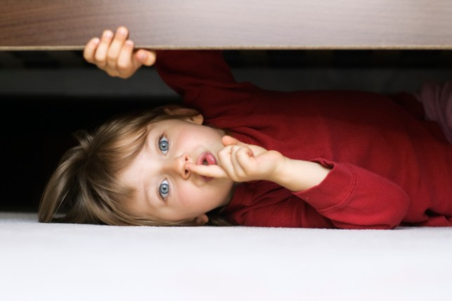 Picture of boy hiding under bed