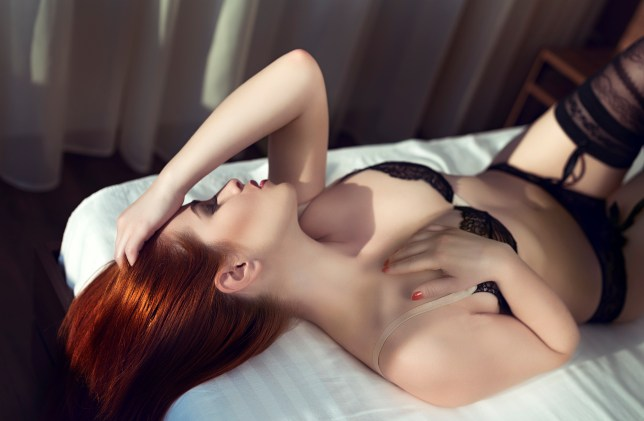 woman in bed lying down and touching herself.