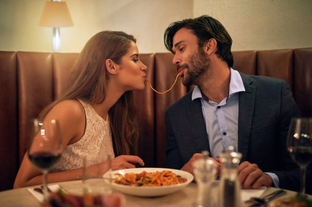 Shot of a young couple sharing spaghetti during a romantic dinner at a restaurant