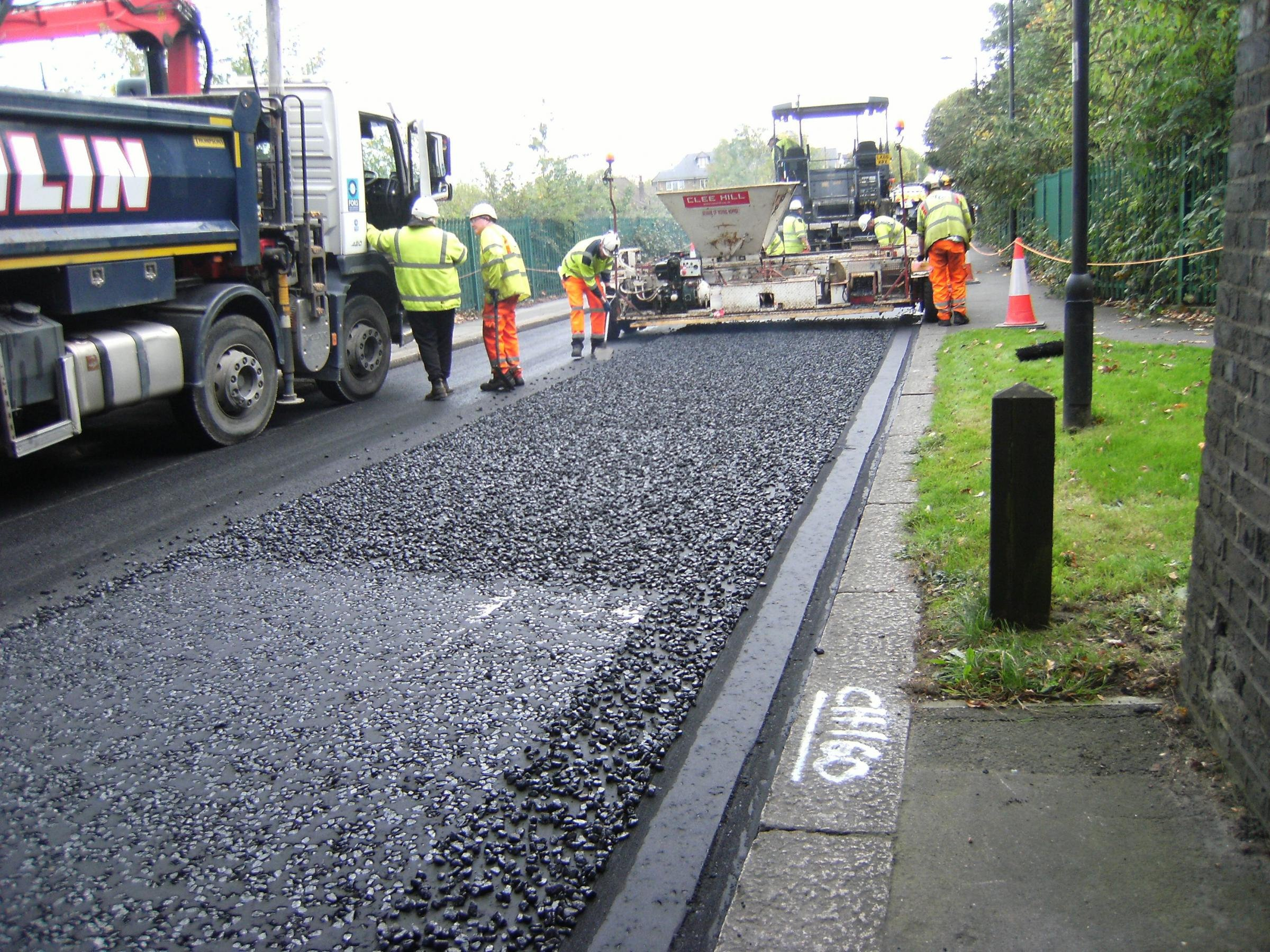 """A council is fighting back against plastic waste - by recycling bottles into ROADS. (Pictured) See National story NNROAD; Enfield Council have already resurfaced one road in a mixture of plastic and asphalt, and are planning on using the pioneering substance on all their streets - because it's tougher than normal. The mix is tougher and more durable than standard tarmac by using waste that would otherwise end up in landfill - and could reduce the number of annoying potholes. Transport for London have given funding to the council plans, which looks to fight the environmental impact of plastic. Monitoring of the road has shown the asphalt mix is performing well and is proving to be a long-term, durable solution to road resurfacing. Enfield Council?s Cabinet Member for Environment, Cllr Daniel Anderson, said: ?We all know that plastics can have a devastating impact on the environment, particularly when the product reaches our seas and oceans. """"We all have a responsibility to step up our efforts to help the environment by recycling more, upcycling and responsibly sourcing materials. ?Enfield Council is delighted with this road trial and hope we can use more of the product across the borough to help divert plastics from landfill and reduce the carbon footprint for road construction.?"""