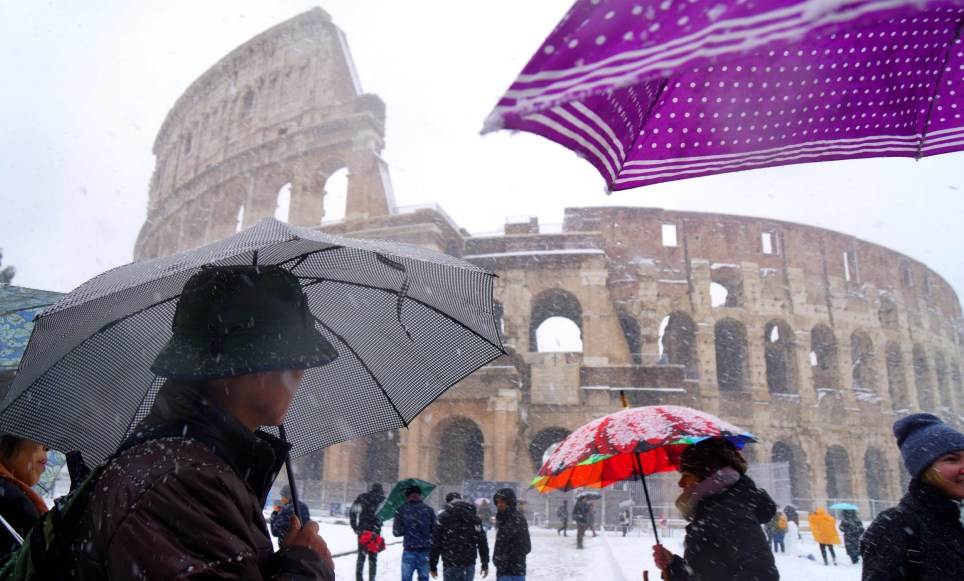 Tourists shed under umbrellas as they visit the ancient Colosseum during a snowfall in Rome on February 26, 2018. / AFP PHOTO / Vincenzo PINTOVINCENZO PINTO/AFP/Getty Images