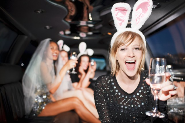 A hen do drinking champagne in a private limousine