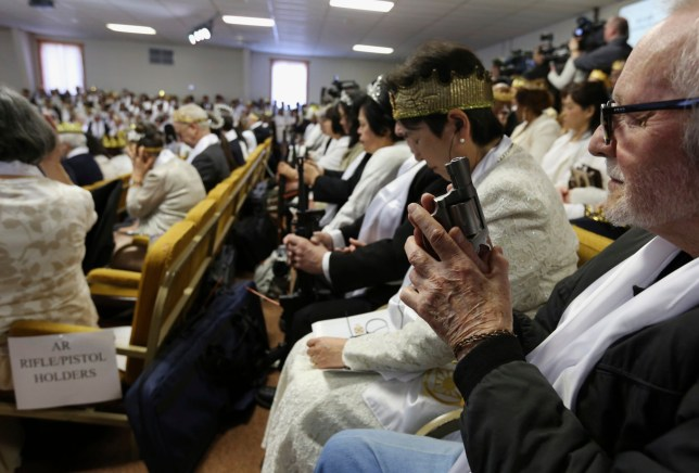 A man holds an unloaded weapon during services at the World Peace and Unification Sanctuary, Wednesday Feb. 28, 2018 in Newfoundland, Pa. Worshippers clutching AR-15 rifles and other weapons participated in a commitment ceremony at the Pennsylvania-based church. The event Wednesday morning led a nearby school to cancel classes for the day. The church's leader, the Rev. Sean Moon, said in a prayer that God gave people the right to bear arms. (AP Photo/Jacqueline Larma)