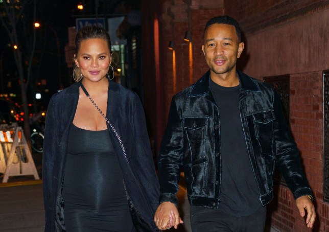 NEW YORK, NY - MARCH 01: John Legend and Chrissy Teigen hold hands when strolling in Soho at night with the Empire State Building in the background on March 1, 2018 in New York City. (Photo by Jackson Lee/Jackson Lee)
