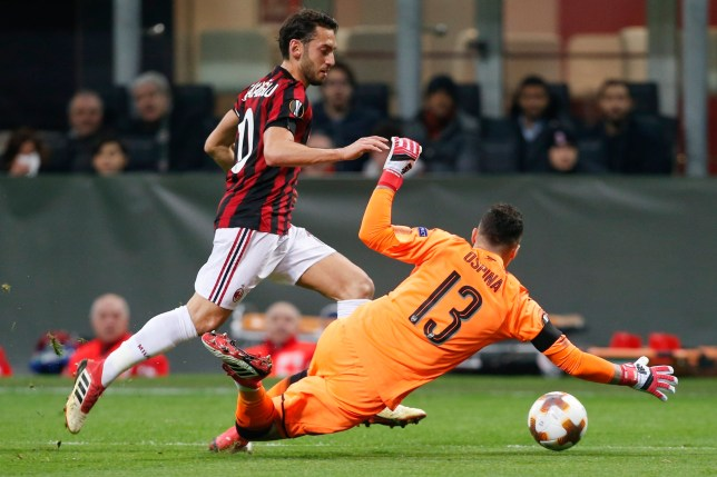 AC Milan's Hakan Calhanoglu takes on Arsenal goalkeeper David Ospina during the Europa League, round of 16 first-leg soccer match between AC Milan and Arsenal, at the Milan San Siro stadium, Italy, Thursday, March 8, 2018. (AP Photo/Antonio Calanni)