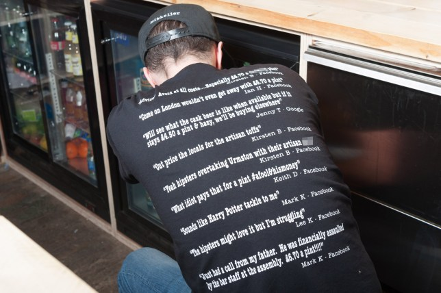 MERCURY PRESS. 12.03.18. Urmston, UK. (Pictured: The Assembly owner Sean Reynolds, 32, wearing his t-shirt that he had printed following some negative reviews on Facebook. )Two bar owners had the perfect response to negative social media comments about their bar by printing them on the back of their uniform. Sean Robinson, 32, and his wife Sophie, 30 decided to see the funny side of the negative comments that were made after customers complained the price of a pint of beer was too high. The Assembly, in Urmston, Greater Manchester, which specialises in craft beers offers beer lovers the chance to sample new beers in either a thirds, half or full pint, with a majority of customers preferring to try several different beers rather than sticking to pints of one beer. Although the price of a pint can sometimes reach ?7 Sean argues that the prices are clearly marked and customers do not have to drink there or pay the price if they don't want to. SEE MERCURY COPY