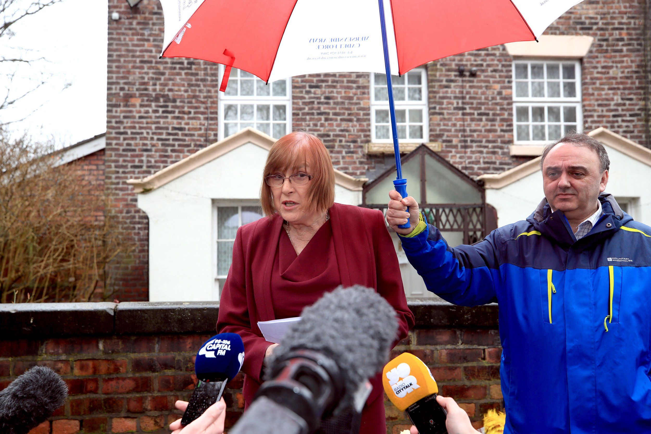 Lady Anne gives a statement outside her Liverpool home following the death of her husband Sir Ken Dodd who has died aged 90, as his nephew John Lewis looks on. PRESS ASSOCIATION Photo. Picture date: Monday March 12, 2018. See PA story DEATH Dodd. Photo credit should read: Peter Byrne/PA Wire