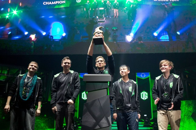 Tal Aizik of European team OG raises the trophy after winning the Boston Major Dota 2 tournament at at the Wang Theatre in Boston on December 10, 2016. Players compete for a 3 millon USD prize pool during the four day tournament. / AFP / Justin Saglio (Photo credit should read JUSTIN SAGLIO/AFP/Getty Images)
