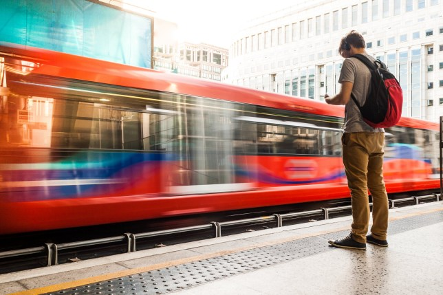 A photo of a young man wearing headphones while waiting for the train. He is on the right side of the image, and a red train is moving in front of him. The train has long windows that reflect the buildings in front of them. The middle section of the train is moving in a blur. There are truncated domes on the sidewalk between the man and the train. The man has short brown hair, and his headphones are black. He is wearing a gray short-sleeved shirt, tan-colored pants, black sneakers and a red and black backpack. A building with many windows is on the other side of the train. He is looking down at his smartphone. Horizontal colour image with copy space.