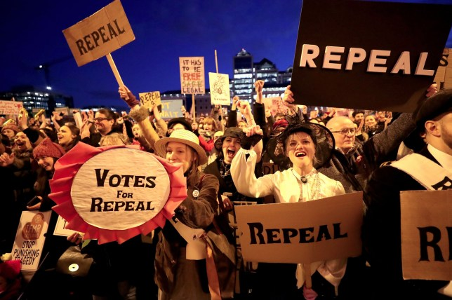 People carrying various signs gather outside The Custom House in Dublin, as participants take part in a march through the city calling for the repeal of the 8th amendment to the Irish constitution.
