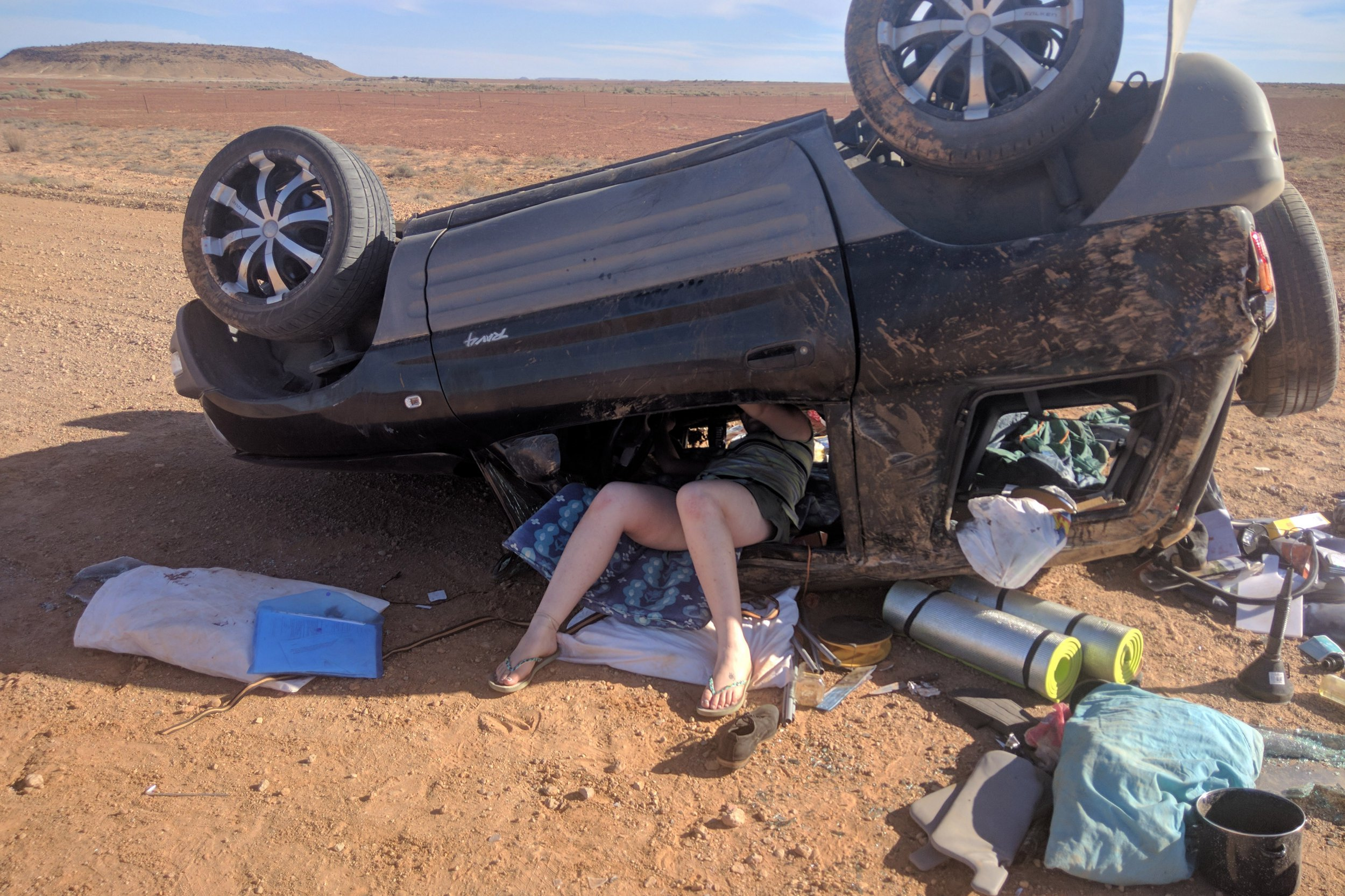 Pics from Brad Warren / Caters News - (PICTURED: Brad is rated at the scene in the upturned car.) What was meant to be a dream holiday for a pair of British backpackers turned into a nightmare when they rolled their car in the Australian outback. Brad Warren, 21, from Sommerset, and Oliver Walker, 22, from Hampshire, lost control and rolled their Toyota Rav 4 four times in the South Australian desert last week. Oliver was left bloodied and unconscious after he was thrown from the window while Brad, who was behind the wheel, was temporarily half-blinded by a scratch to his eye. The mates, who are on a three-month trip down under for their gap year, were miraculously rescued by a passing couple on the Oodnadatta Track before nightfall. - SEE CATERS COPY