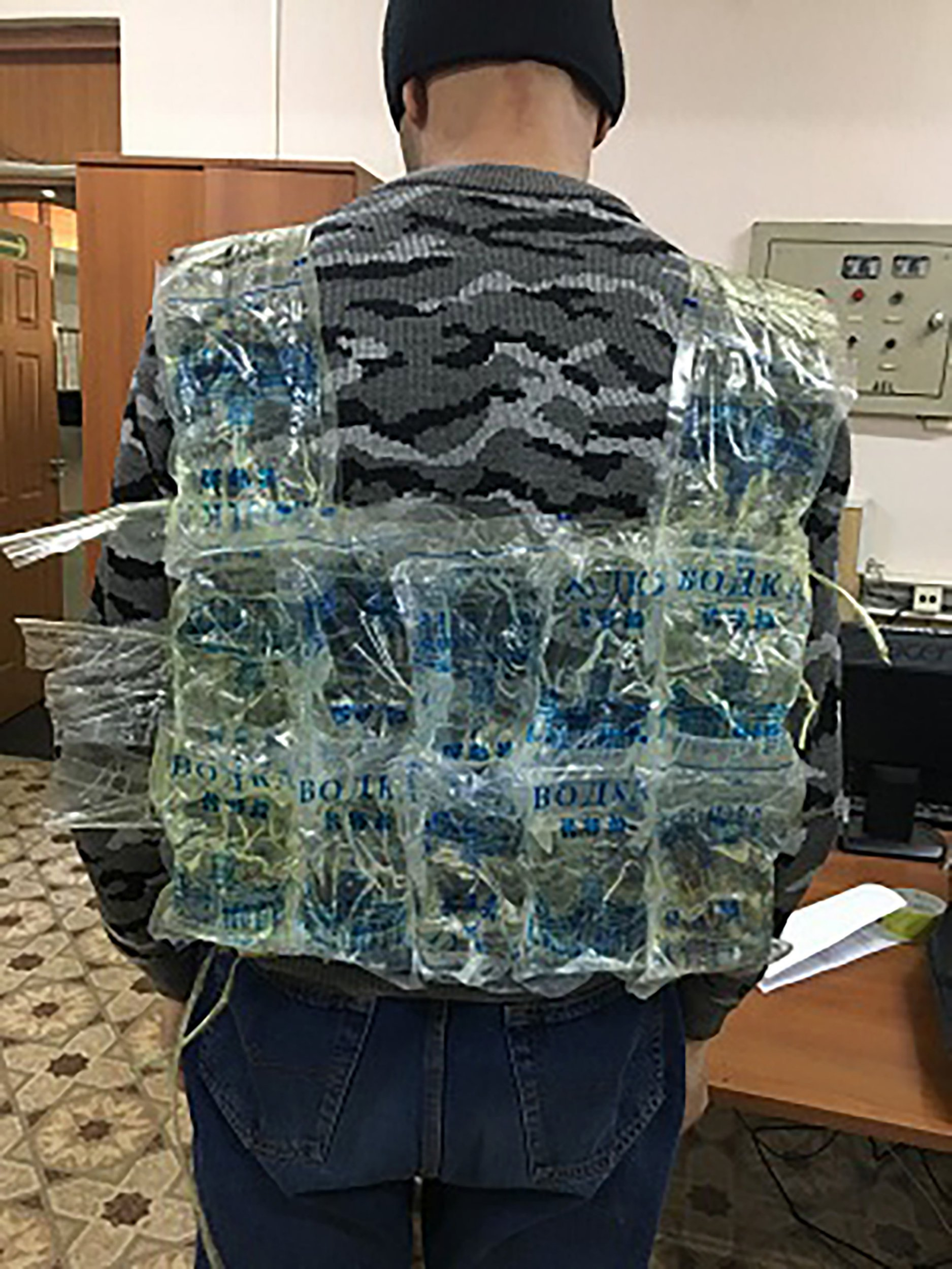 """Pic shows: Tourist with the belt of Chinese vodka Customs officers seized a smuggler who was trying to cross a border wearing a vest made out of 24 plastic bags full of cheap vodka. The man, whose name has not been released, was trying to cross into south-eastern Russia's Zabaykalsky Krai region from China. He had taped together the soft plastic containers of Chinese-made vodka into a vest which he wore underneath his jacket. But customs officers immediately spotted the man's suspiciously bulky body and over-sized jacket and pulled him over for a search. They asked him if he had anything to declare but the man tried to brazen it out and told them that he did not. The man was asked to open his jacket - revealing the 12 litres of smuggled booze in his crude homemade vest. He then told the customs officers that he was bringing the vodka to a party for his brother???s birthday and a wedding. He now faces charges of failing to declare contraband goods to customs officers in a bid to avoid paying excise duties. Netizen ???albo1??? said: """"Did he really have to do so much for this sh*t? He could have made better booze on his own."""" While another online commentator, ???Uynachalnica???, added: """"He should have done a better job of hiding it under his jacket."""" Zabaykalsky Krai has an extensive 998-kilometre (620-mile) border with China."""