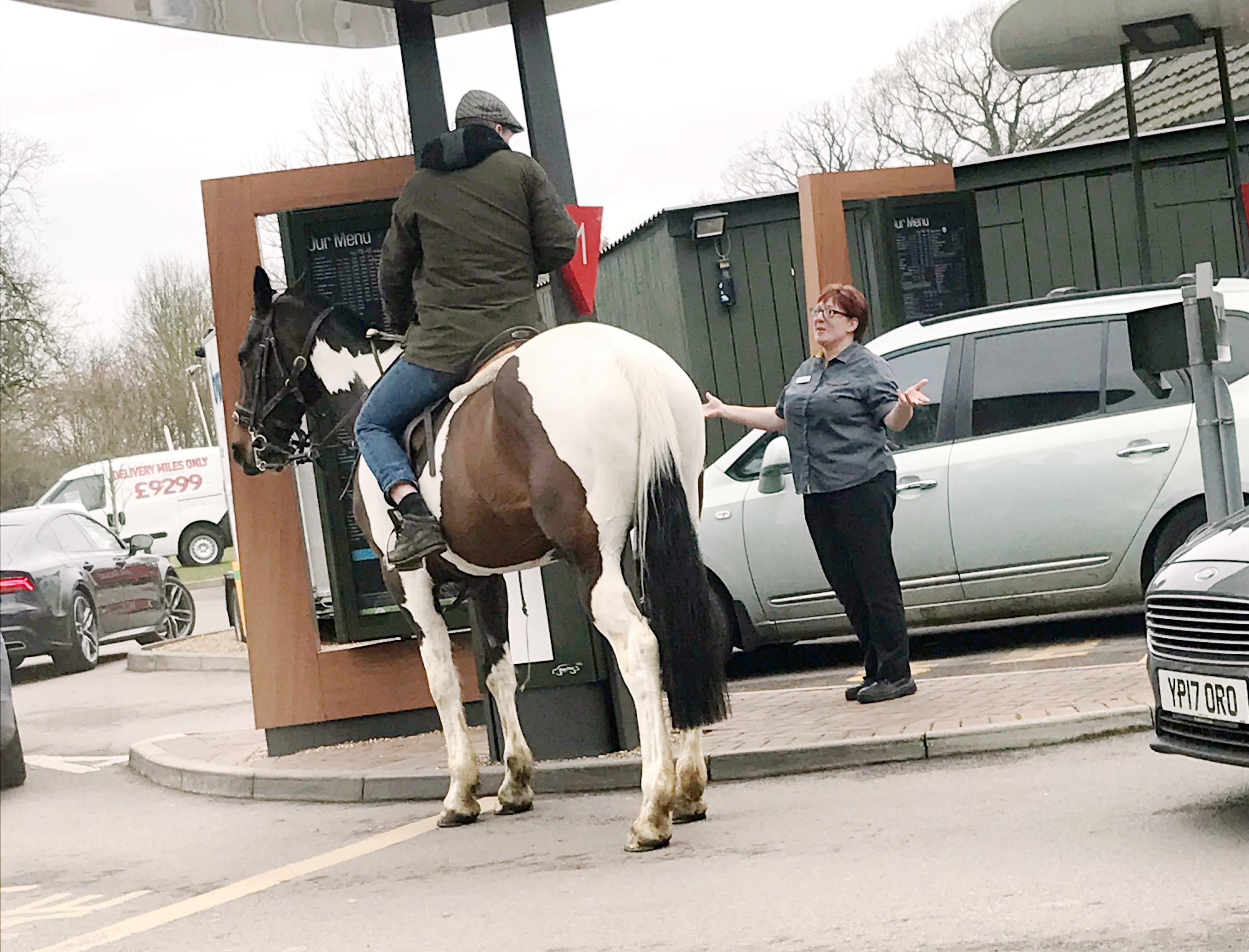 """A man on a horse tries to order at McDonalds in Beccles, Suffolk. See Masons copy MNHORSE: This is the hilarious moment a man tried to ride a HORSE through a McDonald's drive-thru - before being told 'neigh'. Bemused customers were surprised to see the rider """"trotting up"""" to the kiosk before trying to place an order for his 'mane' course. But he was stopped in his tracks by a member of staff who told him he had to dismount."""
