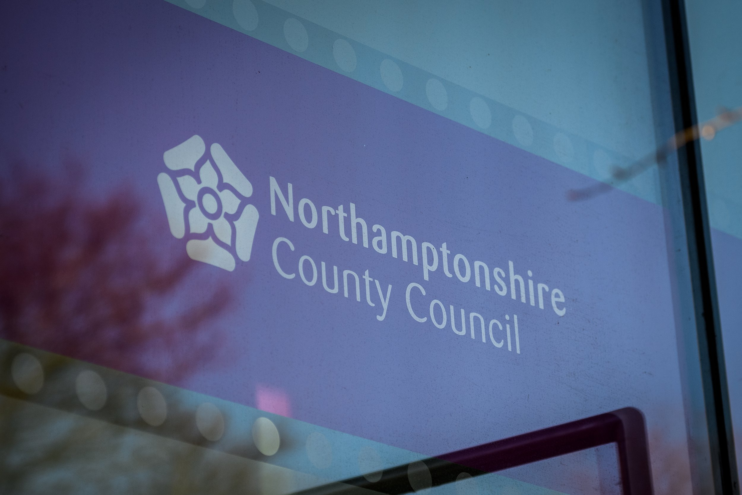 NORTHAMPTON, UNITED KINGDOM - FEBRUARY 15: The Northamptonshire County Council logo is seen in the window of the new One Angel Square office block near the town centre on February 15, 2018 in Northampton, United Kingdom. Northamptonshire County Council has banned all new spending after announcing an overspend of ??21m for the 2017-18 period. As it attempts to pay off ??150m of loans, the council is looking at selling it's new ??53m headquarters at One Angel Square, which was only opened in October 2017. (Photo by Leon Neal/Getty Images)
