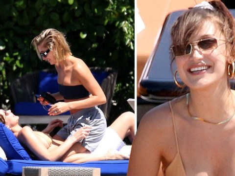 Hailey Baldwin straddles Bella Hadid as models giggle in their bikinis during day on the water