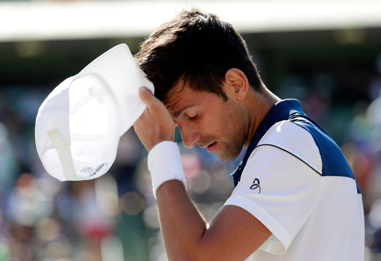 Novak Djokovic holds his forehead with cap in hand as he struggles in a match in 2018